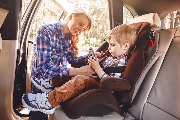 Мать пристегивает своего мальчика, который сидит в машине на семейной дороге в кресле безопасности
