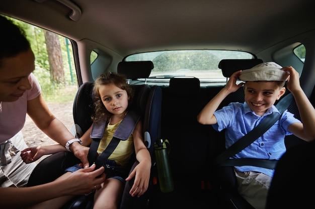 Мать крепления ее милая дочь к детскому сиденью безопасности внутри автомобиля. дети на автокресле безопасности в автомобиле