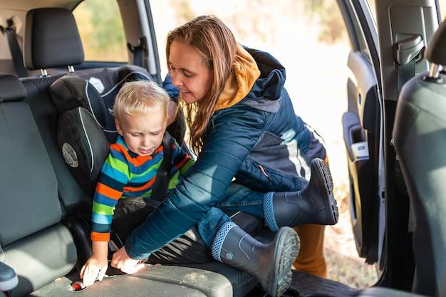 母親が男の子の安全ベルトをチャイルドシートに固定している。