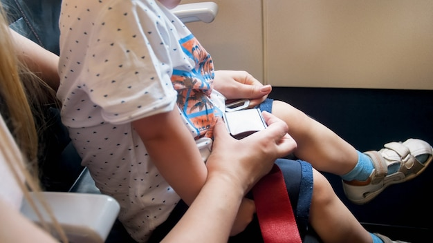 Mother fastens safety seat belt of her child in airplane before flight.
