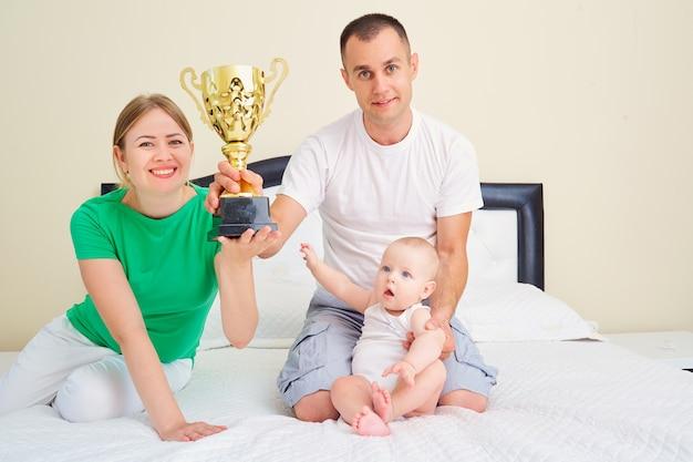슈퍼 가족과 슈퍼 영웅의 개념을 함께 침대에 컵 챔피언 어머니 아버지와 아기