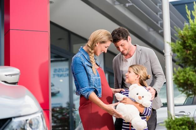 Мама, папа и ребенок покупают машину в автосалоне