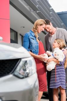 대리점에서 자동차를 구입하는 어머니, 아버지 및 자녀
