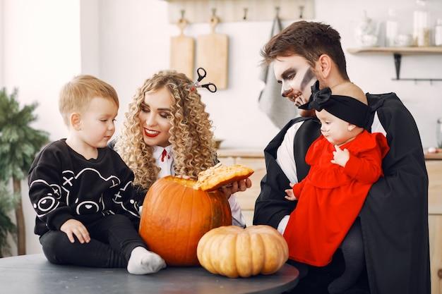 Мать, отец и дети в костюмах и макияже. семья готовится к празднованию хэллоуина.