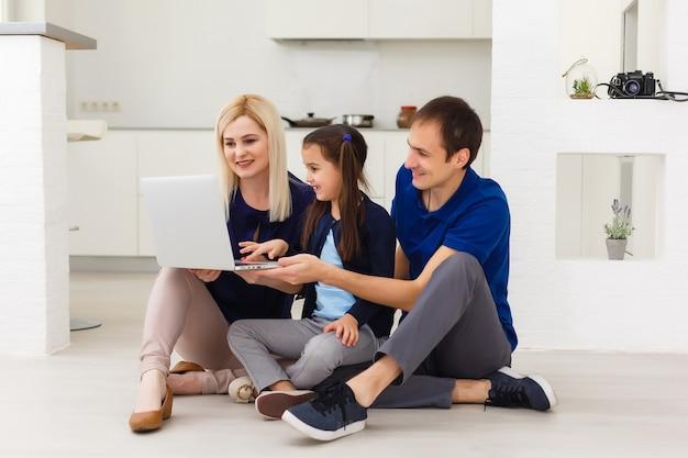 Мать, отец и дочь учатся на ноутбуке. социальное дистанцирование и самоизоляция в условиях карантина