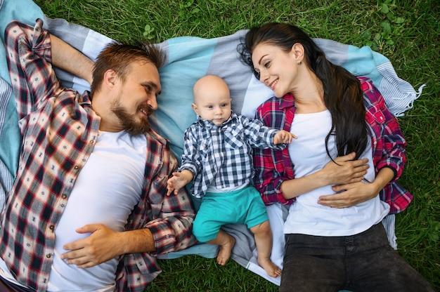 어머니, 아버지와 잔디에 작은 아기 레저