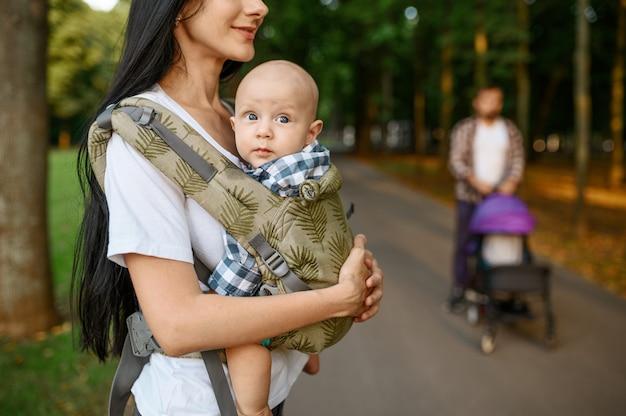 어머니, 아버지, 여름 공원에서 골목을 따라 걷는 작은 아기