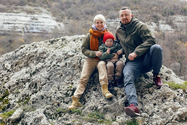 Мать, отец и сын, ребенок путешествуют по пещерам в теплой одежде осенью