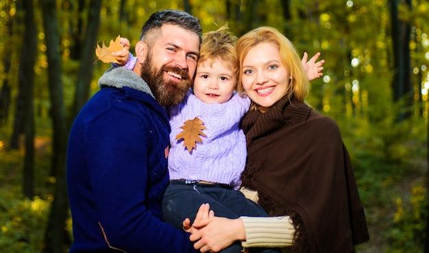秋の母、父、息子が公園を散歩します。晴れた日に親子で一緒にリラックス。