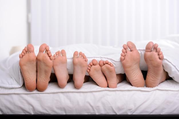 Мать, отец и двое детей лежат на кровати с белыми простынями
