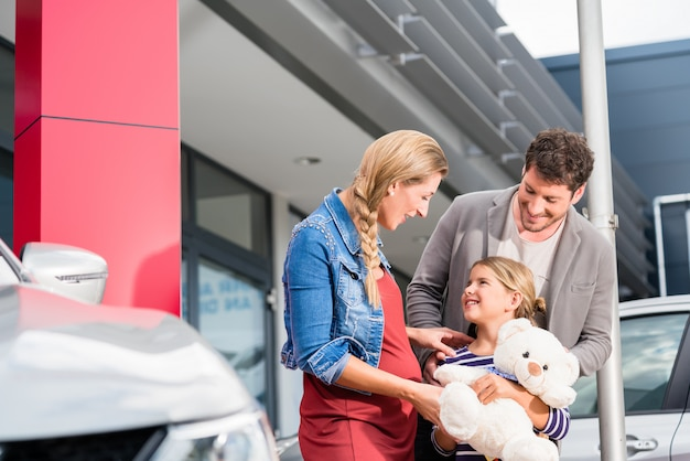 Mother, father, and child buying car at dealership