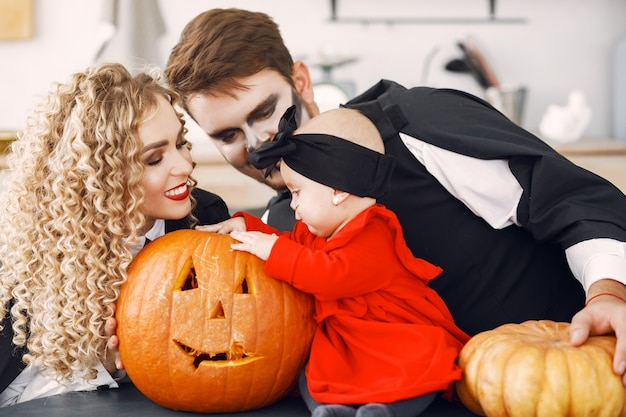Mother father and children in costumes and makeup. family prepare to celebration of halloween.