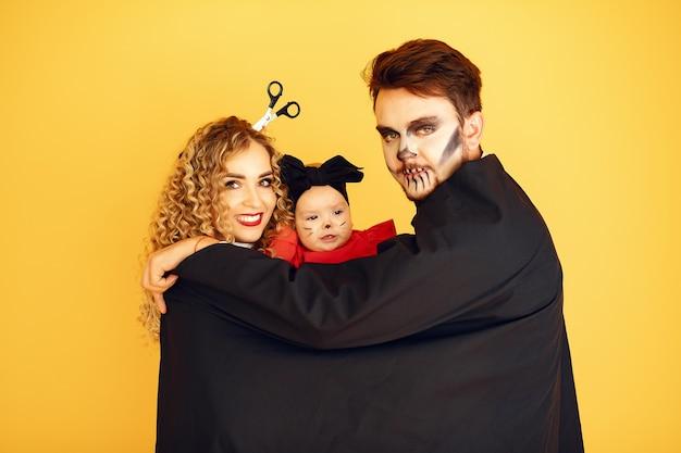 Madre, padre e figli in costume e trucco. persone in piedi su uno sfondo giallo.