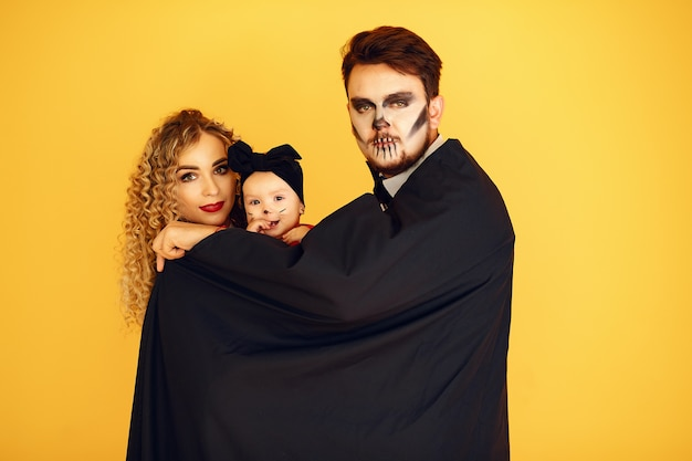 Mother father and children in costumes and makeup. people standing on a yellow background.