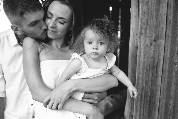 Madre, padre e figlia insieme divertendosi in fattoria