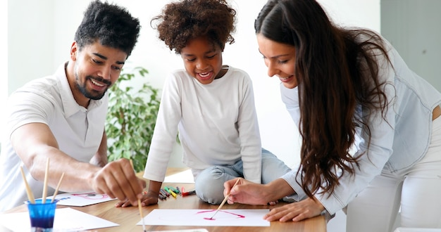 Mother and father drawing together with their child at home