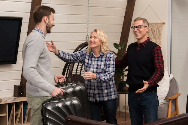 Mother and father going to embrace son at home