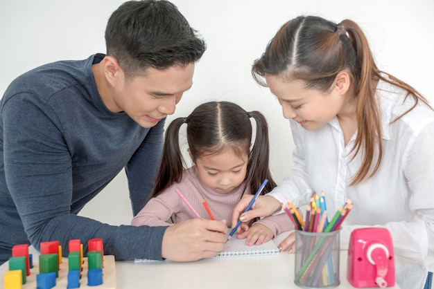 Mother and father help their daughter do homework in living room