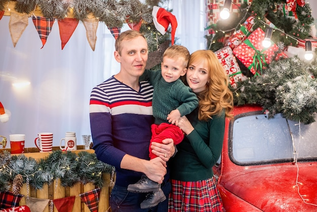 Mother and father hug the boy. new year and christmas. a happy family is having fun with their son