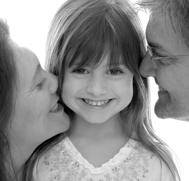 Mother and father kissing daughter, smiling, portrait (b&w)
