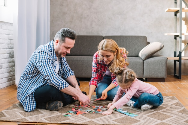 Mother and father playing puzzle pieces with their daughter