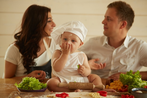 The mother, father and small child sit on the table near dough and vegetables