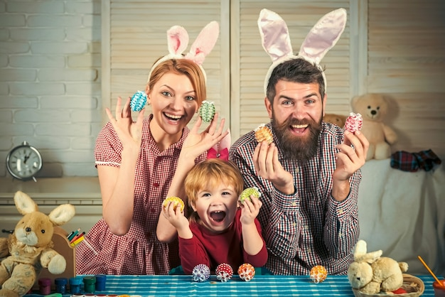 Mother, father and son are painting eggs. happy easter family. cute little child wearing bunny ears