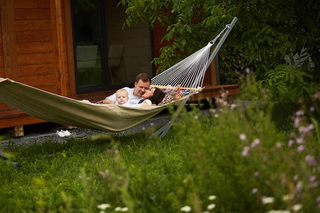 The mother,father and son lie on the hammock