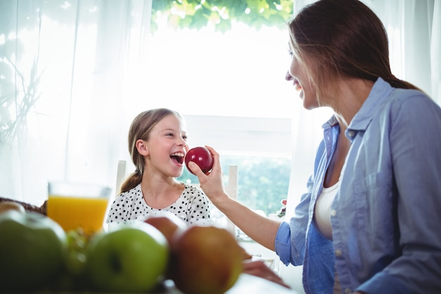 Mother feeding apple to her daughter while having breakfast