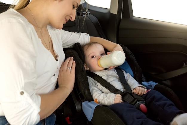 Mother feeding baby boy with milk on car back seat