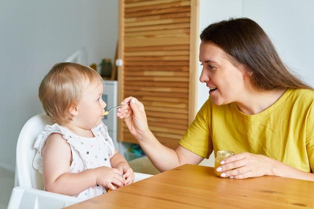 Мать кормит ребенка ложкой, мама дает еду ребенку дома, малыш сидит на стульчике