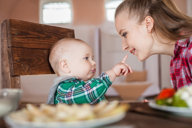 母親が子供を養っている。幼い子供のための最初の固形食品。