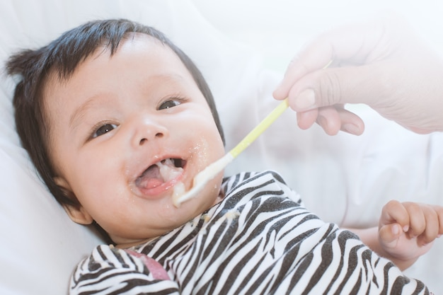 Mother feeding cute asian baby girl with a spoon at home