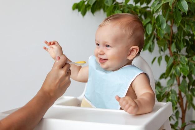 スプーンから青いよだれかけでかわいい金髪の赤ちゃんを養う母