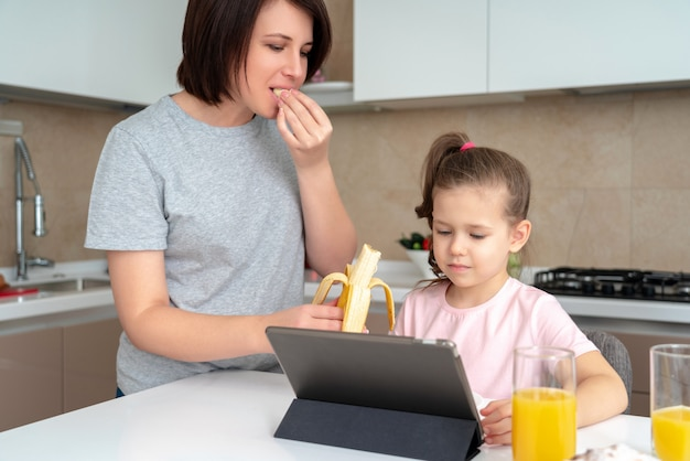 Mother feeding daughter with banana at the table in modern kitchen, single mother family