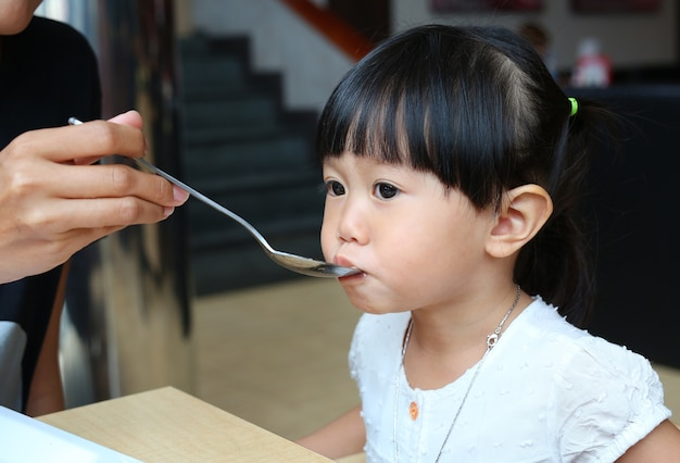 Mother feeding food on spoon for her kid.