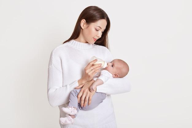 Мать кормит ребенка из бутылочки, изолированного на белом