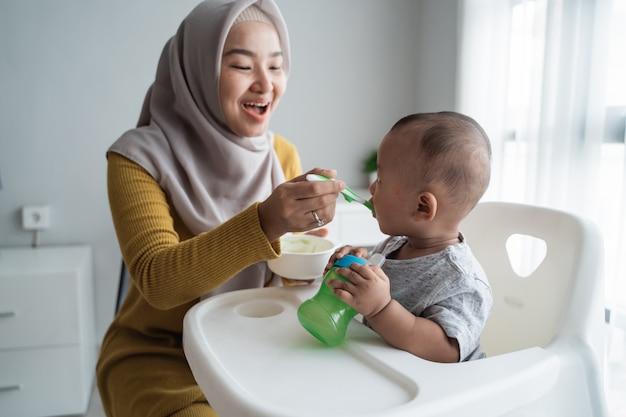 높은 의자에 앉아있는 동안 그녀의 아기를 먹이 어머니