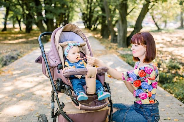スプーンで彼女の女の赤ちゃんを授乳する母親。彼女の愛らしい子供に食べ物を与える母。かわいい赤ちゃんのベビーカーキャリッジの上に座って、笑顔のポーズ