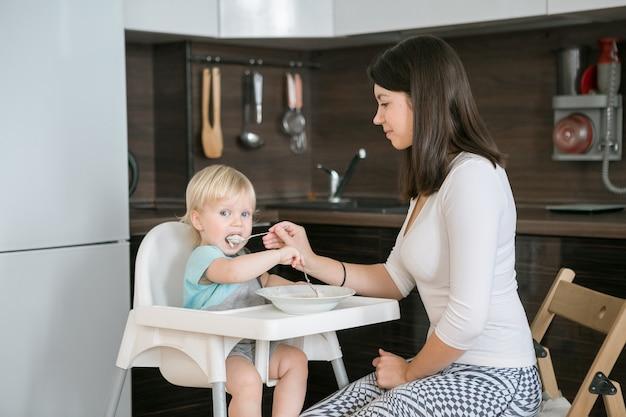 그녀의 아이를 먹이 어머니. 한 살짜리 아이를 위한 첫 번째 고형식. 아기가 높은 의자에 앉아 있거나 대여합니다. 엄마와 어린 소년은 죽을 먹는다. 어린이를 위한 건강한 영양. 부모는 부엌에서 아이들에게 먹이를 줍니다.