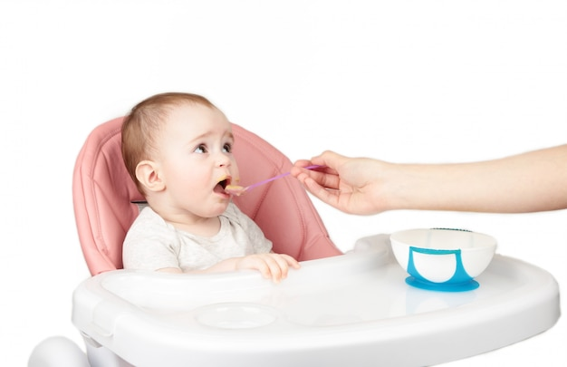 Mother feeding her cute baby girl in chair isolated on white background.