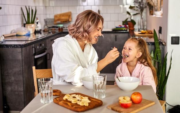 Мать кормит дочь ложкой, ест кашу, свежие фрукты на кухне