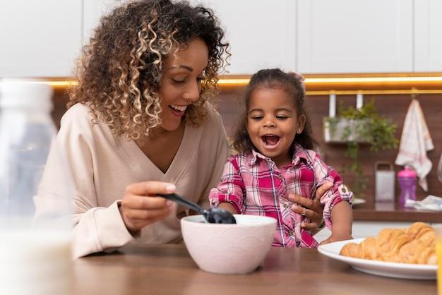 台所で娘に餌をやる母