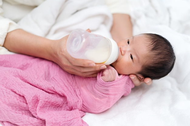 ベッドの上で生まれたばかりの赤ちゃんに牛乳瓶を与える母親