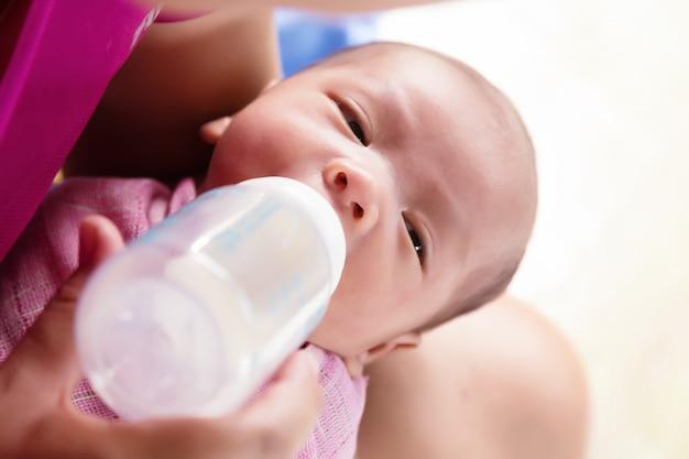Mother feeding newborn baby boy with milk in nursing bottle.