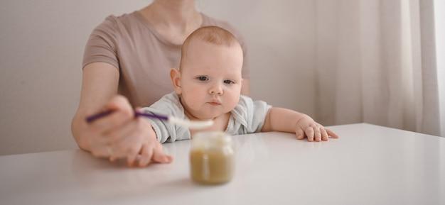 그녀의 작은 신생아 아기에게 숟가락으로 유리 항아리에서 야채 또는 과일 퓌레를 먹이는 어머니