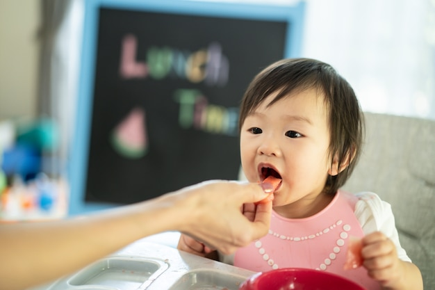 Mother feeding watermelon to young cute kid on baby high chair feeding seat at home, enjoy eating meal and open mouth to eat sweet fruit.