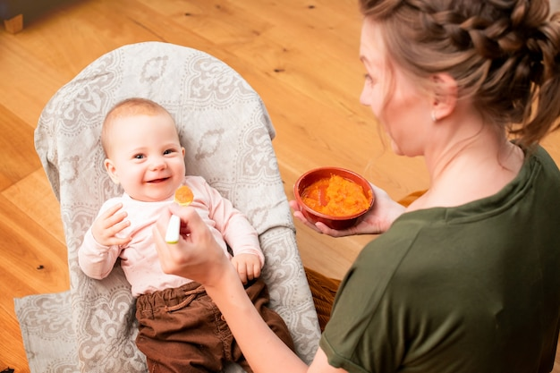 Мать кормит смеющегося ребенка овощным пюре из пластиковой ложки дома.