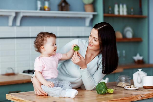 母は赤ちゃんのブロッコリーと野菜を養います