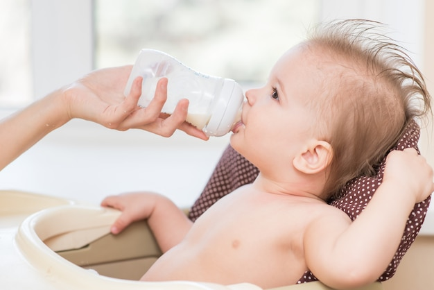 Mother feeds baby from a bottle of milk